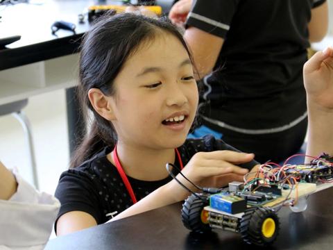 センサーとモーターを組み込んだマシーン型ロボットと女の子の写真