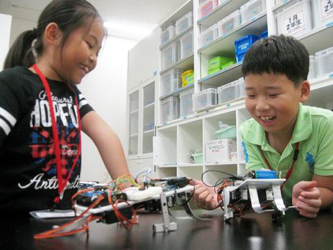 センサーとモーターを組み込んだ二足歩行ロボットと男の子と女の子の写真
