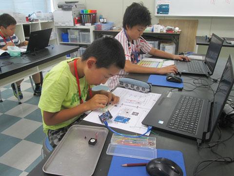 電子工作する子どもたちの写真